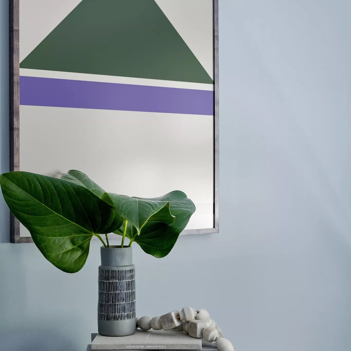 Art piece over entryway with large plant leaves.