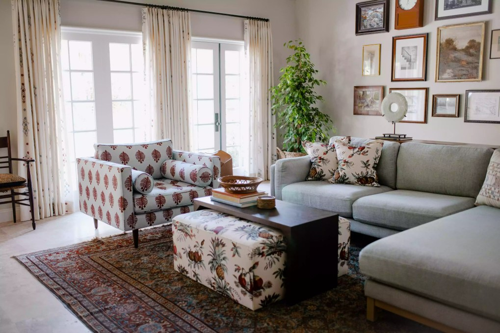 Living room with floral ottoman and pillows.