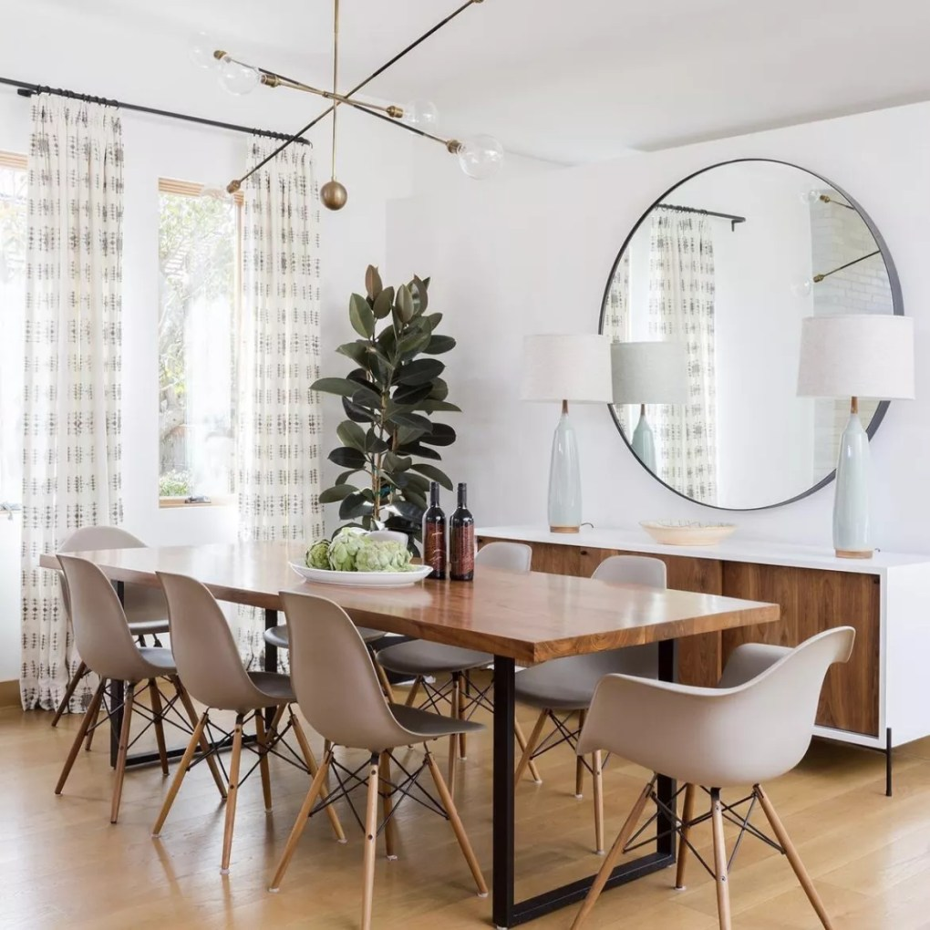 Neutral dining room with Eames style chairs and large mirror