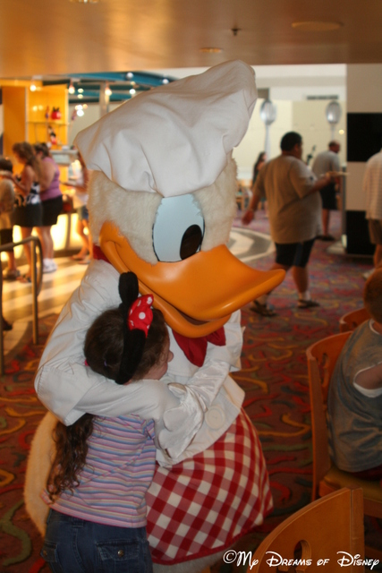 Sophie hugs on Donald Duck at Chef Mickey's!
