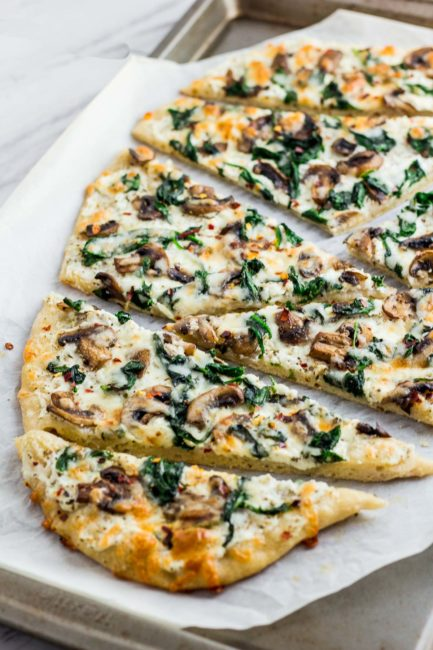 Whole mushroom and spinach white pizza cut up in the baking sheet after baking in the oven