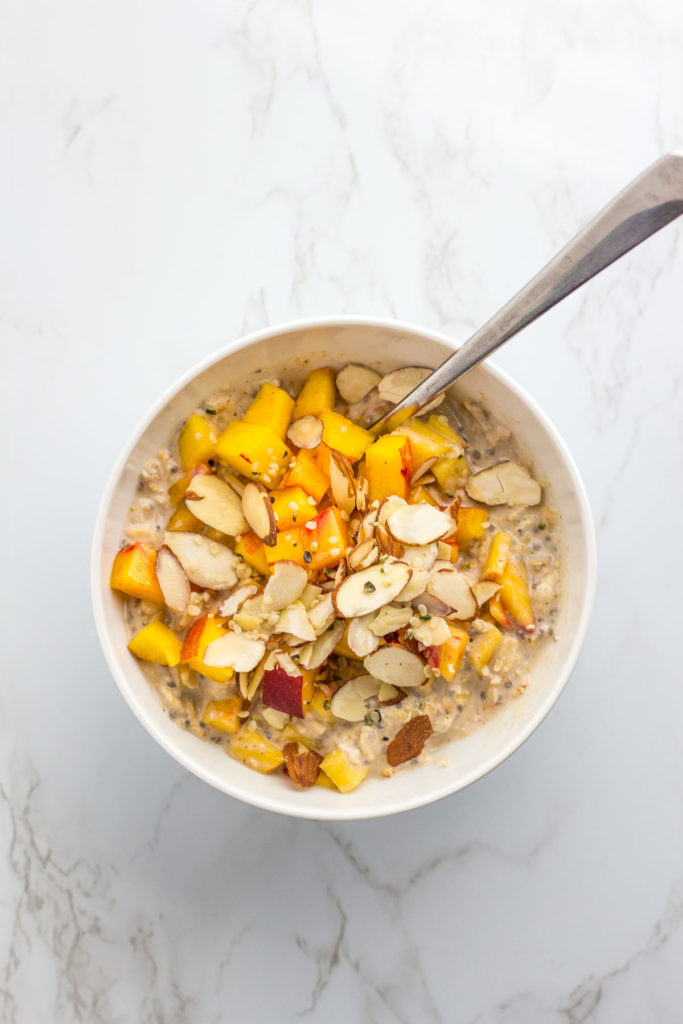 Overnight oats in a white bowl with diced peach, hemp seeds, and sliced almond on top