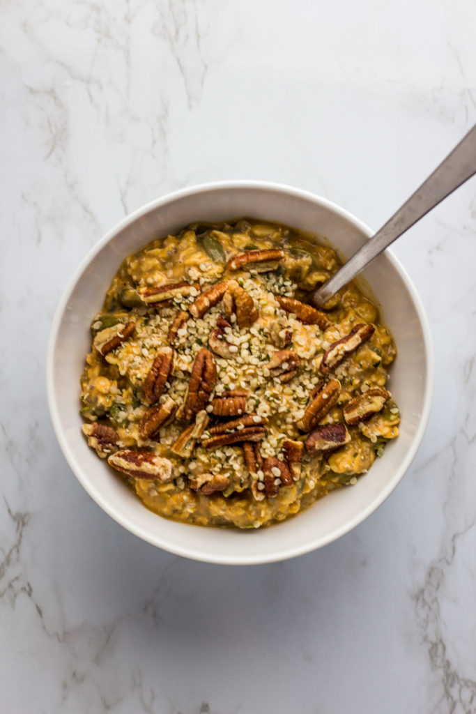 overnight oats in a white bowl with pumpkin puree, pumpkin spice, and pumpkin seeds. Sprinkled of pecan halves with hemp seeds