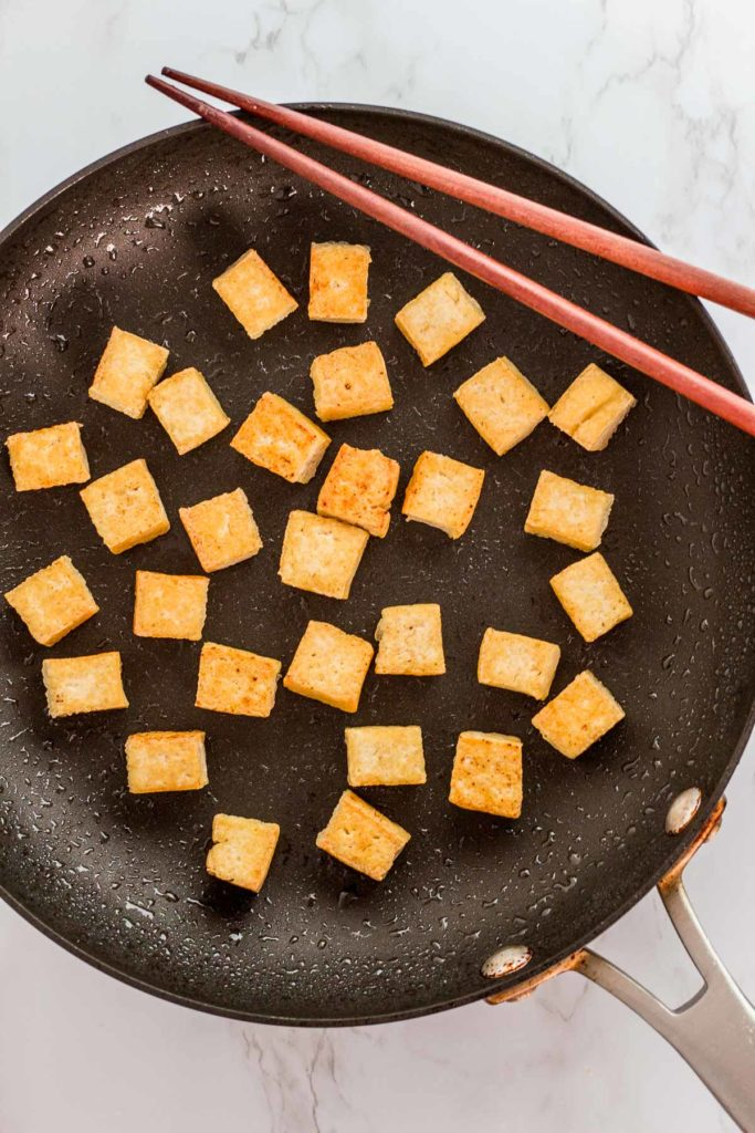 corn starch dusted tofu cubes being fried on a non-stick skillet with chopsticks