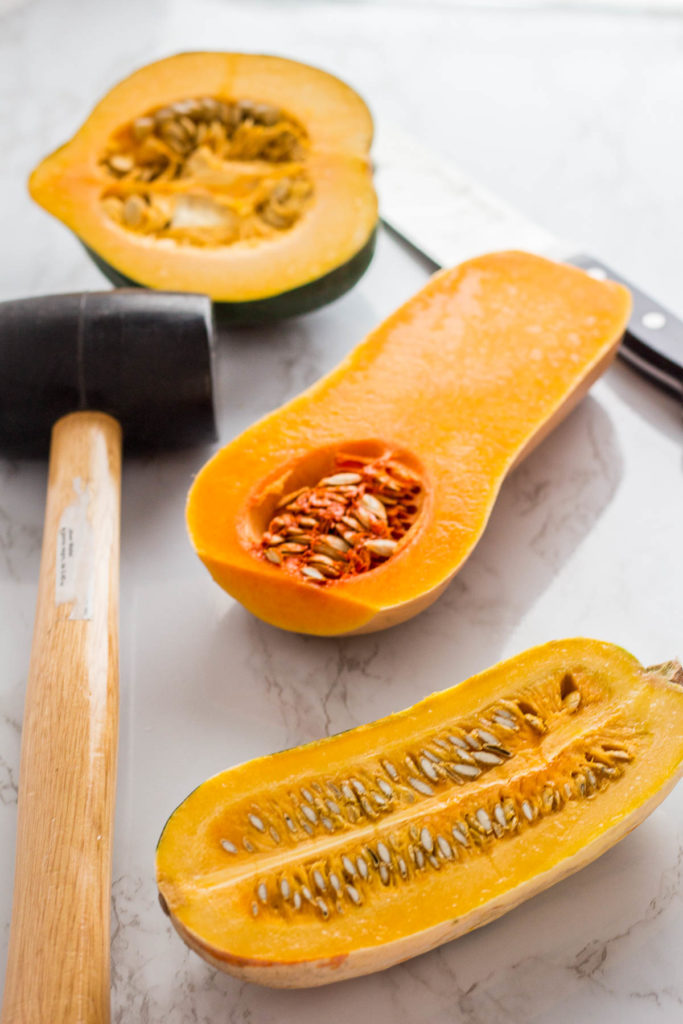 Halves of acorn squash, butternut squash, and delicata squash with rubber mallet and knife