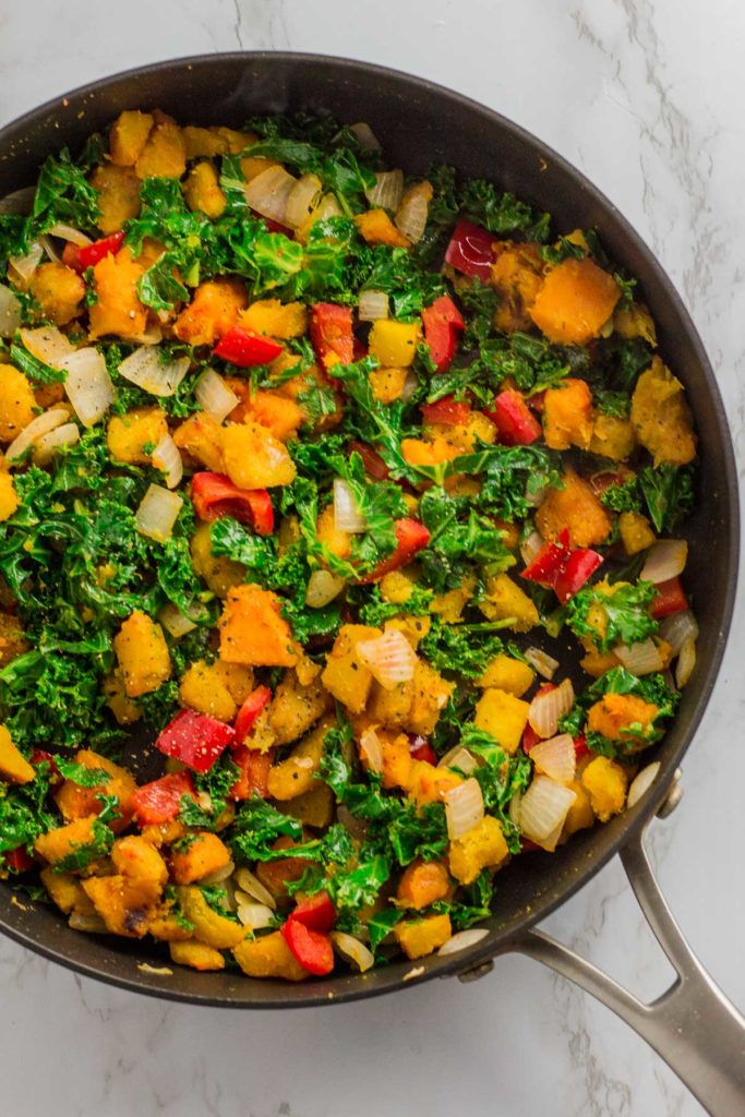 Cooked onion, red bell pepper, winter squash, and kale in the pan