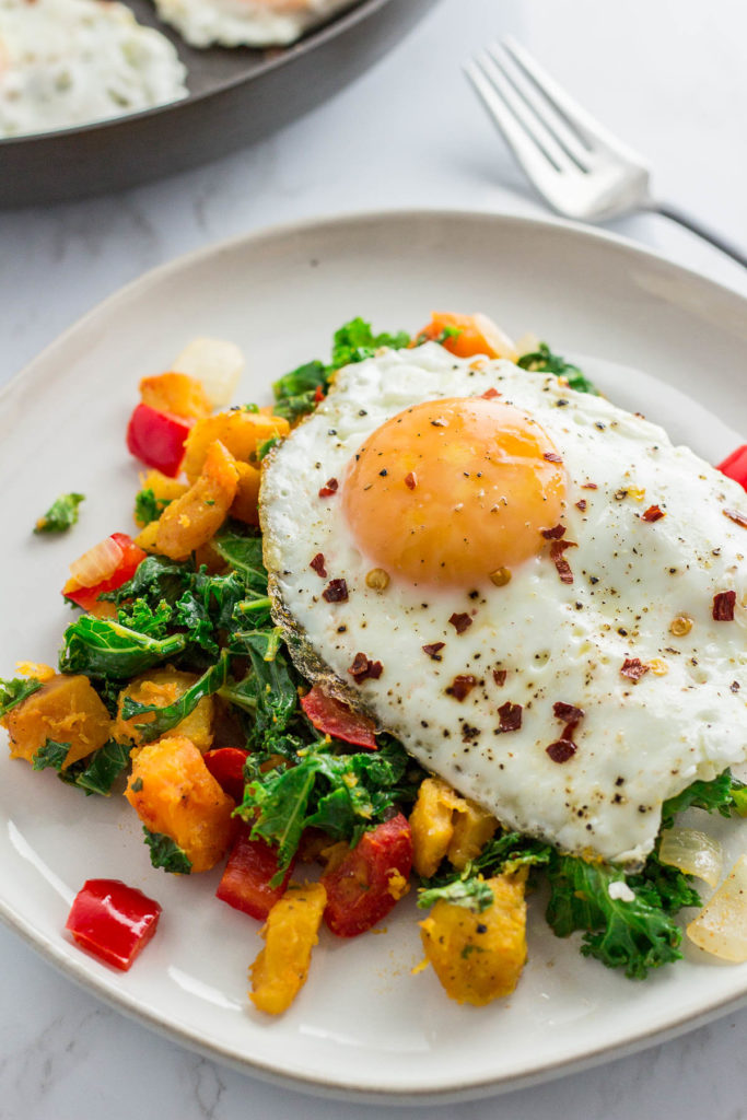 winter squash kale hash on a white plate with fried egg on top