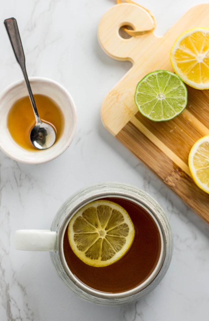 over head shot of cold fighting tea with lemon and honey next to prepared tea