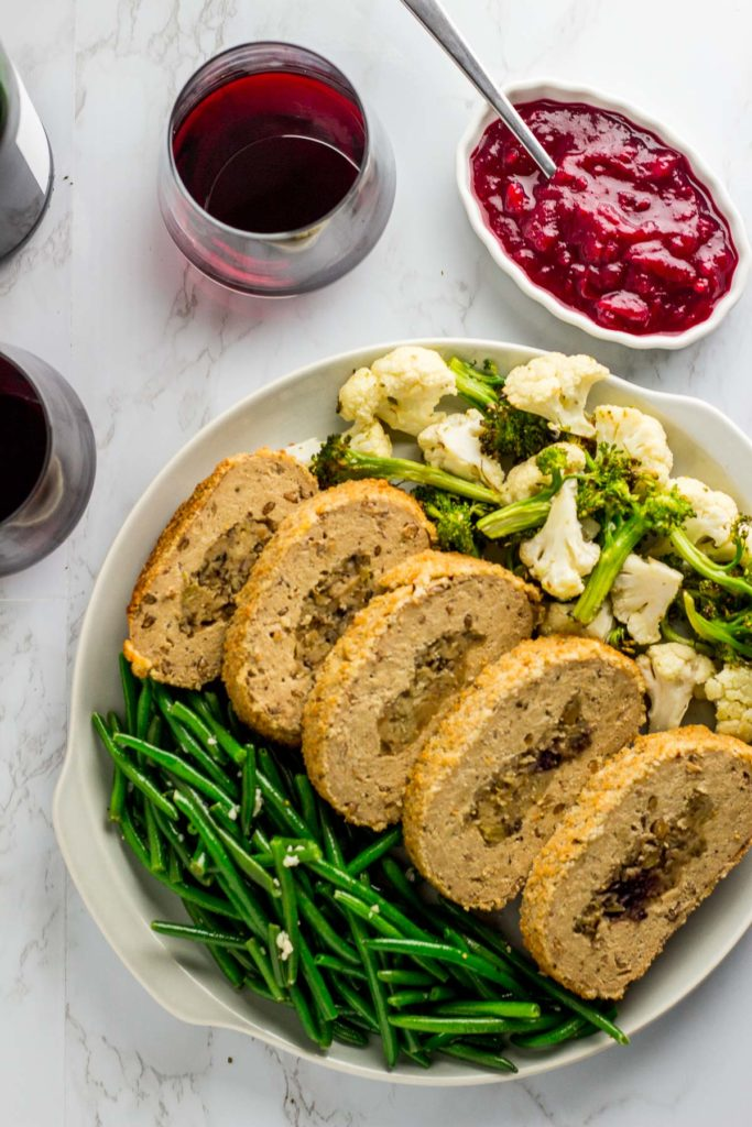 Sauteed green bean, vegan turkey, and roasted broccoli and cauliflower on a plate with side of cranberry sauce and red wine in the background