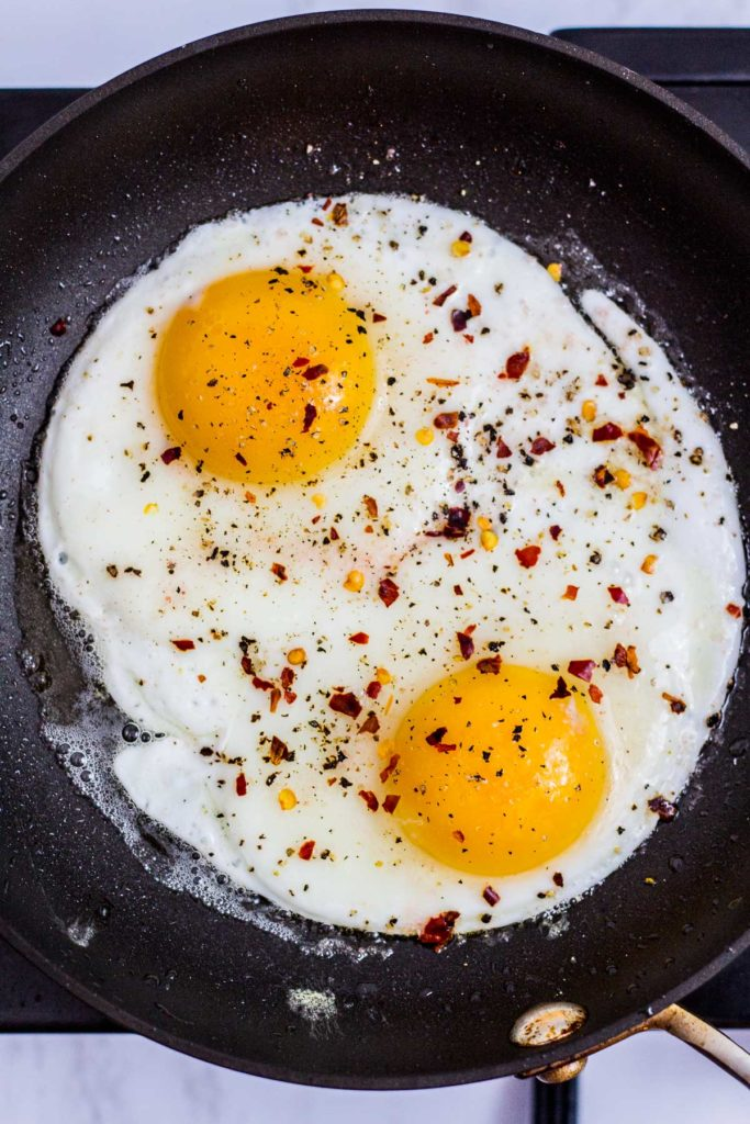 Two fried eggs in the pan seasoned with salt, pepper, and red pepper flakes