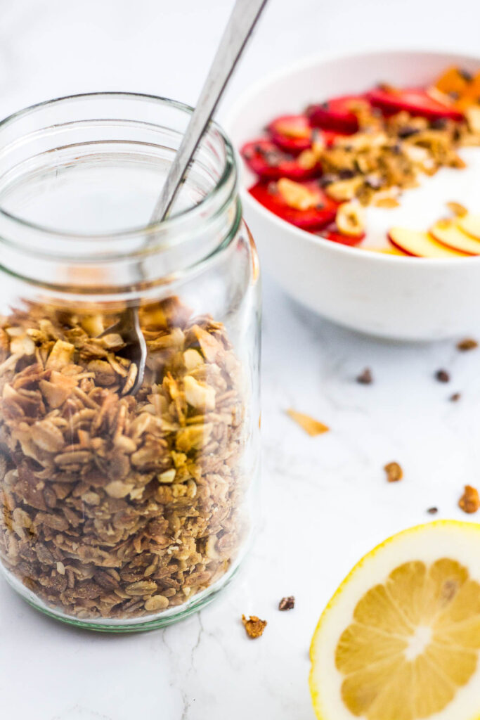 a clear jar half full of granola and yogurt bowl in the background