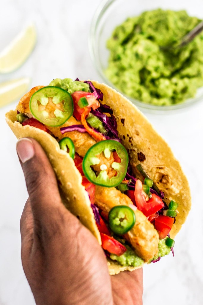 holding a prepared vegan fish stick taco in hand. Guacamole and lime wedges in the background