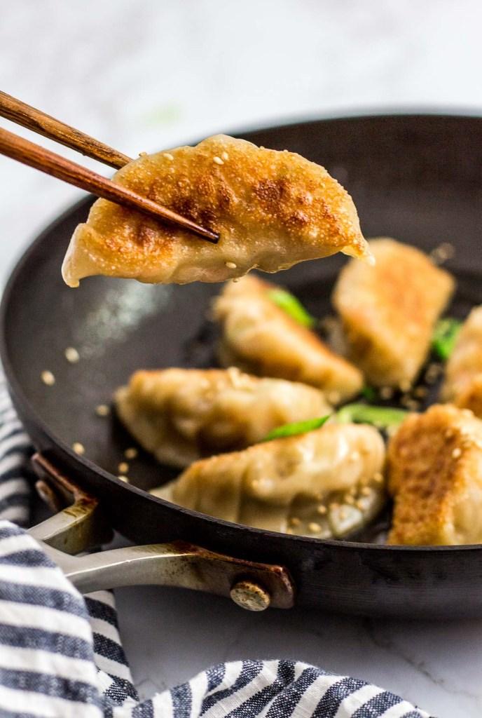 holding a pan fried Homemade Korean Veggie Tofu Mandu/dumpling with chopsticks from a pan