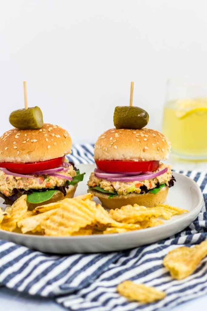 two mini canned chickpea salad sandwiches on a plate with some potato chips and pickles