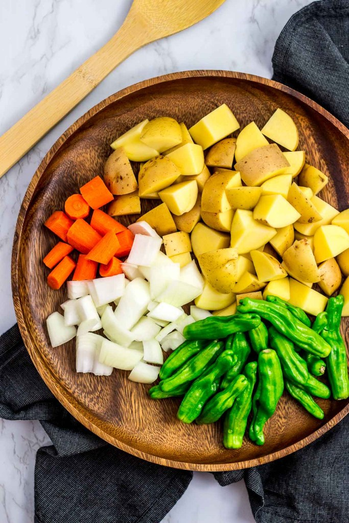 Potato, carrot, onion and shishito peppers on a wooden plate
