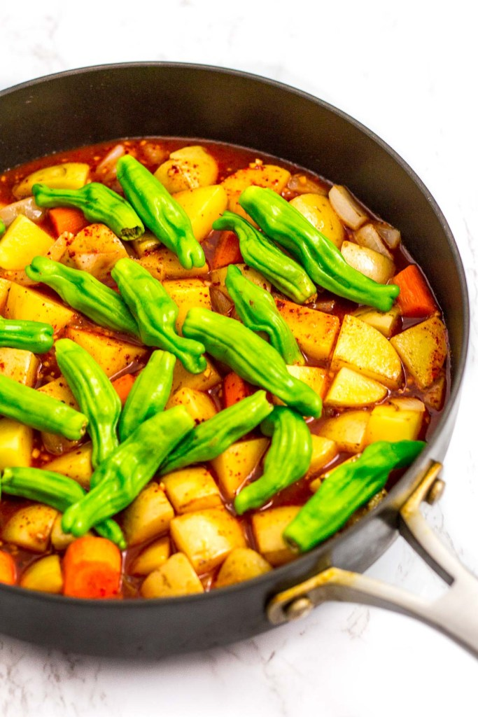 sauce and water is added to browned potato, carrot, onion and shishito pepper in the skillet