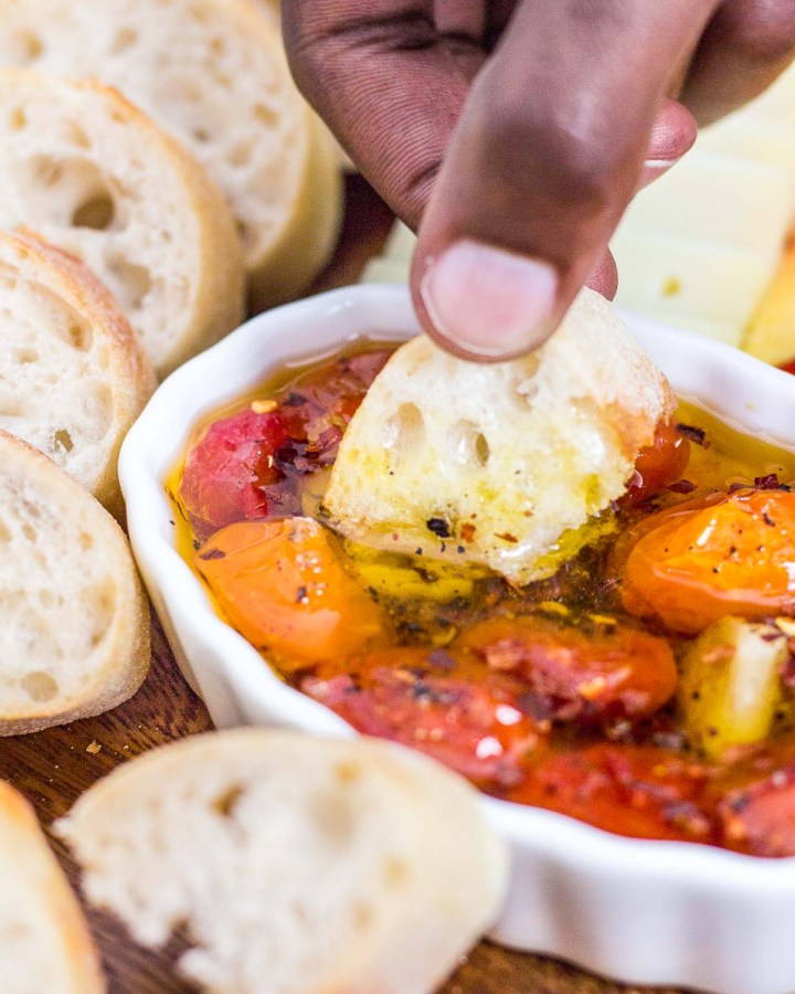 dipping baguette in cherry tomato and garlic oil