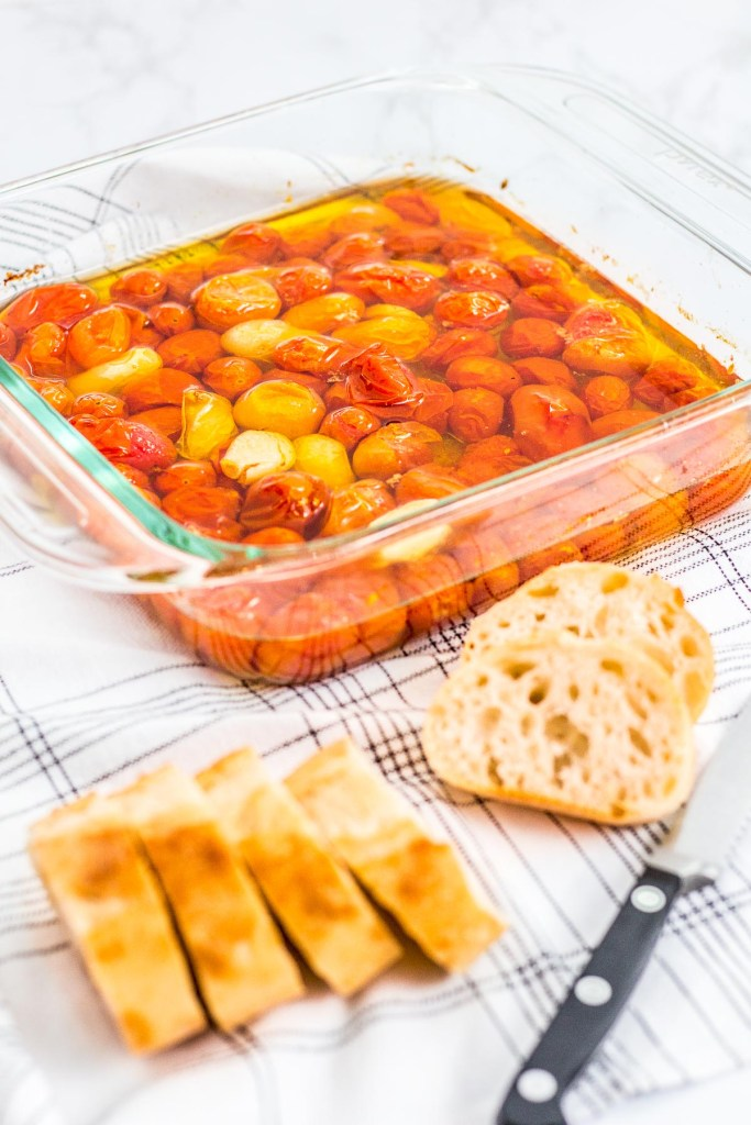 slow roasted cherry tomatoes with some sliced baguette bread in front