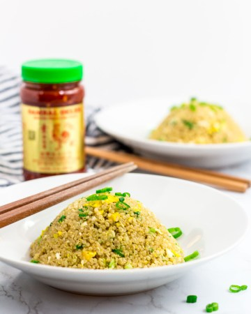 two bowls of healthy egg quinoa fried rice with chili garlic sauce in the background