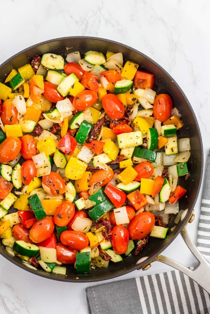 sautéed vegetables (onion, tomato, zucchini, and pepper) in the skillet