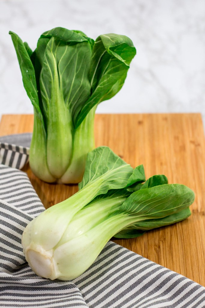 two unwashed bok choy on a wooden cutting board
