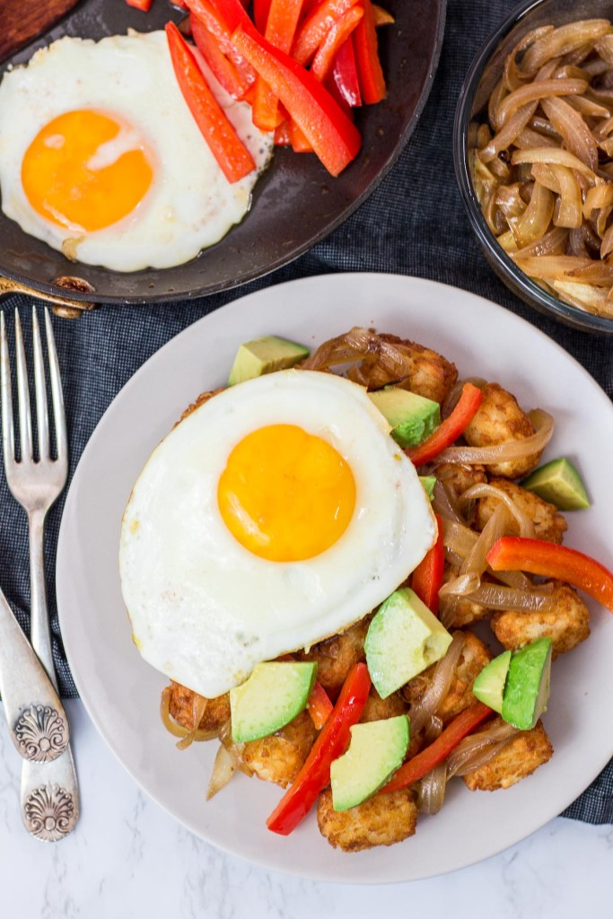 tater tots, pepper, onion, avocado, and an egg on a plate