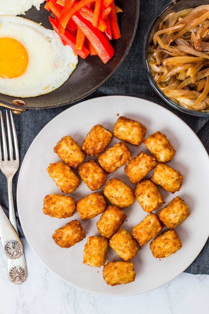 air fried tater tots on a plate, caramelized onion, sauteed pepper, and fried egg in the background