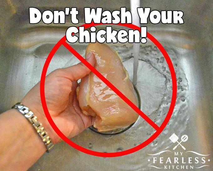 a hand holding a raw chicken breast under running water
