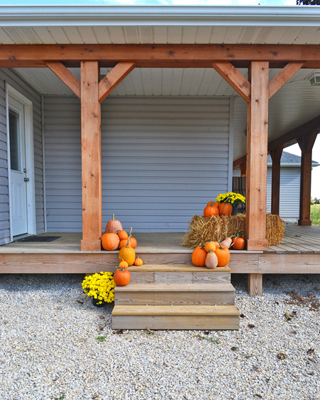 back porch decorated for fall with pumpkins, mums, and straw bales