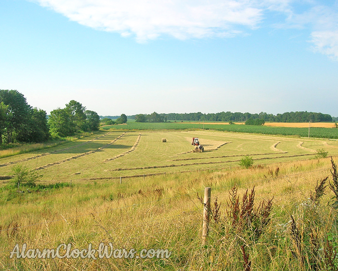 A hay baler, baling hay in a partially raked field, seen from above.