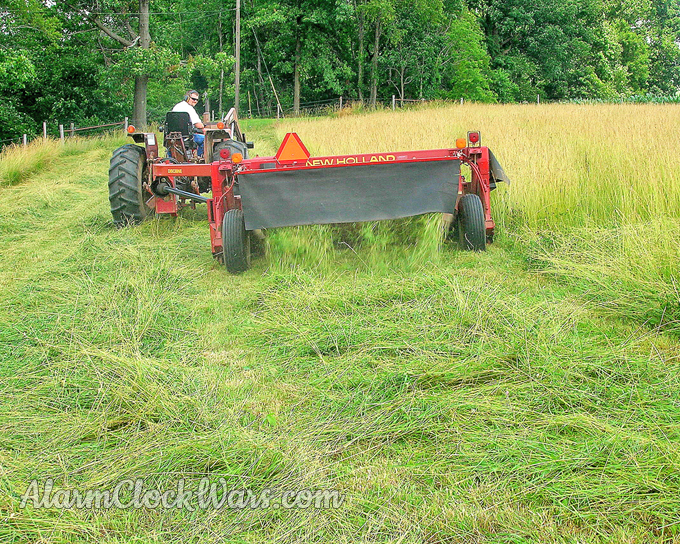 The tractor pulls the mower-conditioner. The mower is offset from the tractor.