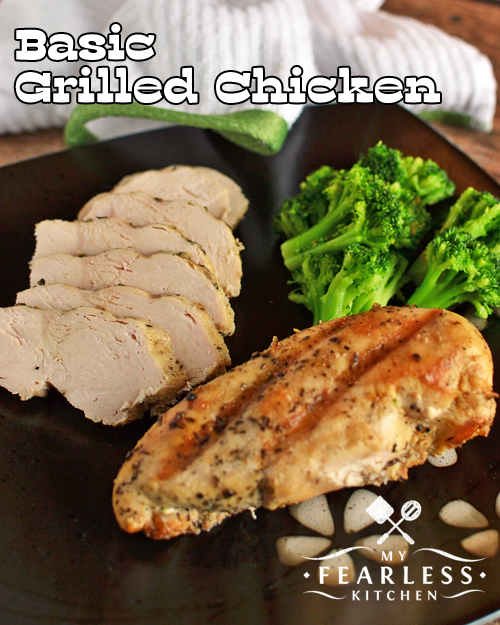 grilled chicken breast and broccoli on a dark plate with a white and green napkin