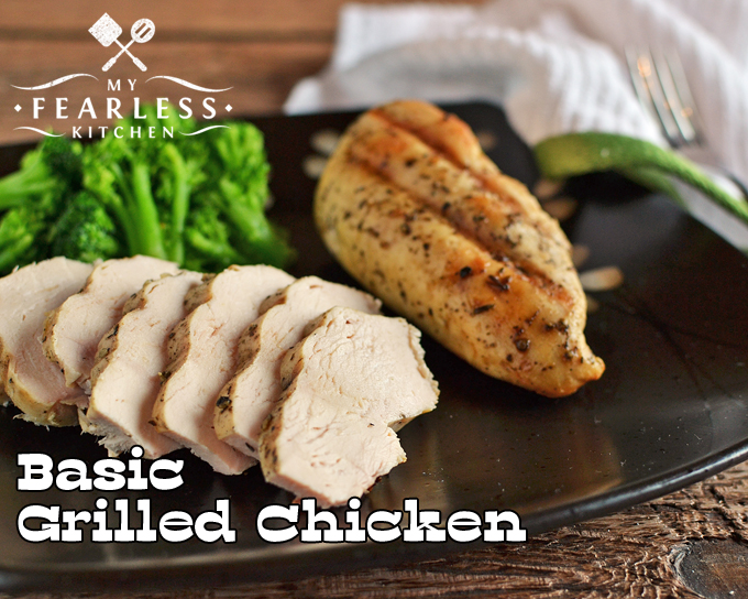 sliced grilled chicken breast on a dark plate with broccoli