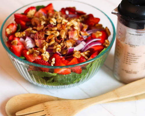 big bowl of strawberry spinach salad topped with bacon, onions, and nuts