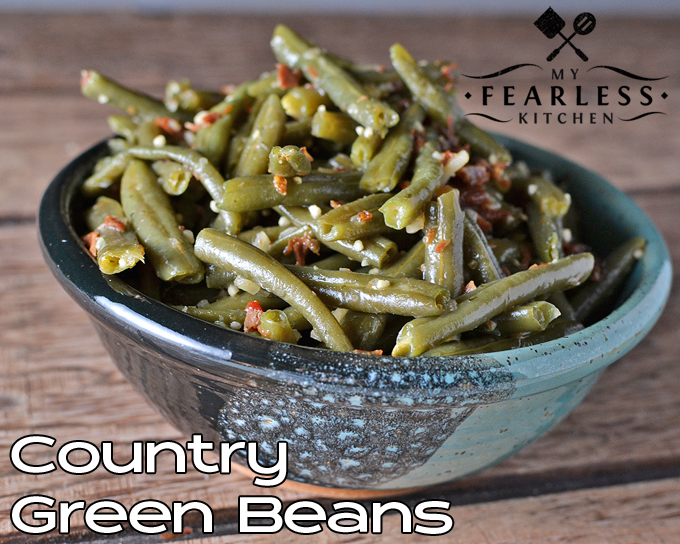 a green and black bowl of green beans with bacon on a wooden background