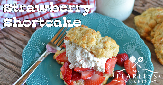 strawberry shortcake with fresh whipped cream on a blue plate