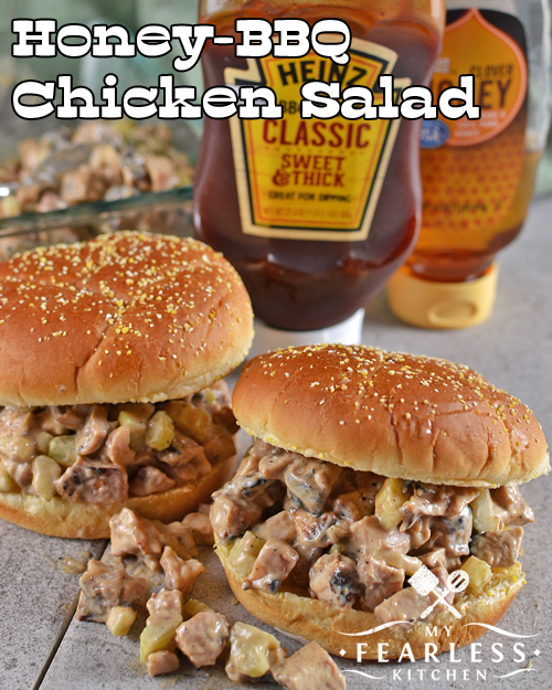 two honey-bbq chicken salad sandwiches in front of bottles of bbq sauce and honey