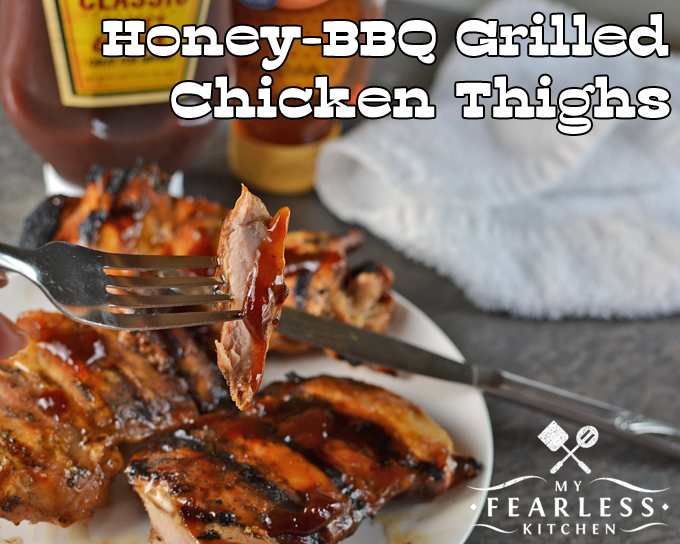 a fork holding a piece of Honey-BBQ Grilled Chicken Thighs with honey-bbq sauce