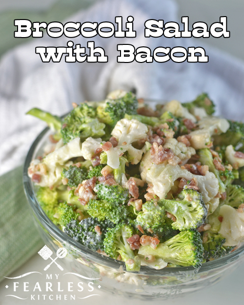 a glass bowl of broccoli, cauliflower, and bacon salad