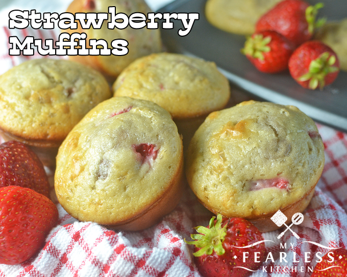strawberry muffins with fresh strawberries on a red and white checked napkin