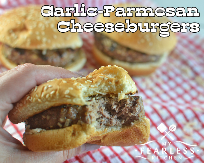 a thick garlic-parmesan cheeseburger on a sesame seed bun with a bite taken out