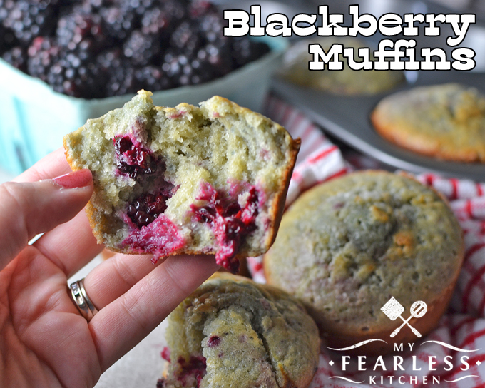 a hand holding half of a blackberry muffin with more muffins and fresh blackberries in the background
