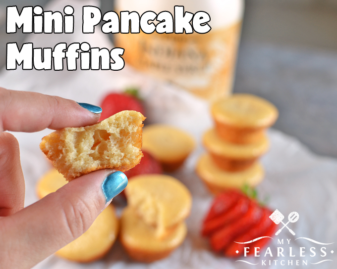 a hand holding a fluffy Mini Pancake Muffin with more in the background