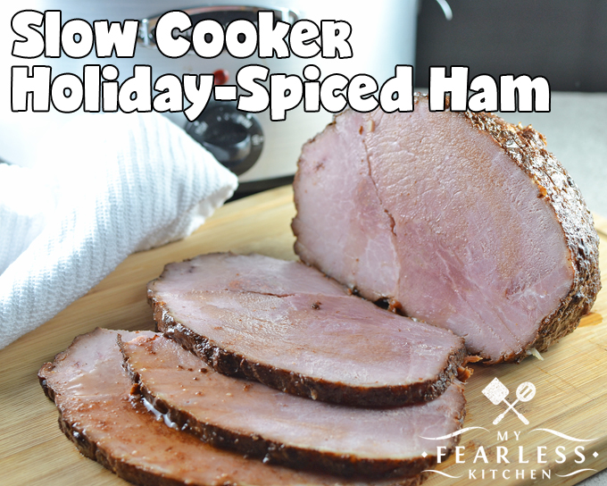 boneless sliced ham on a wooden cutting board in front of a slow cooker