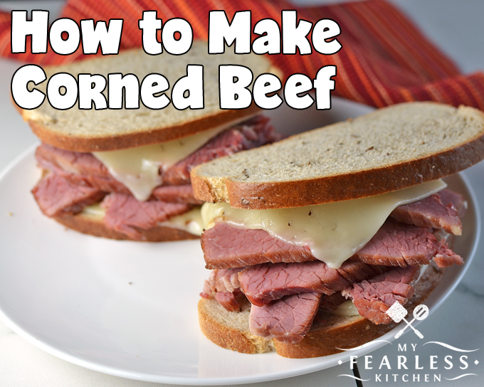 two thick corned beef sandwiches with melted swiss cheese on rye bread