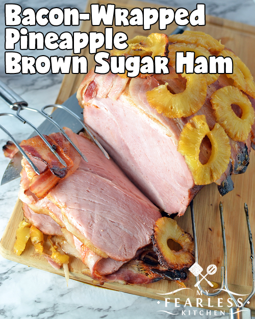 partly sliced boneless ham wrapped in bacon with pineapple rings