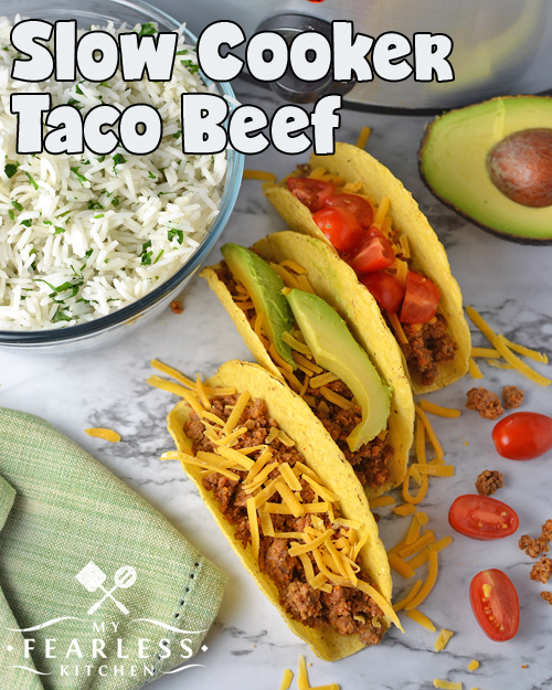 overhead view of three beef tacos topped with cheese, avocado, and tomato, with rice, extra avocado and tomatoes, and a slow cooker