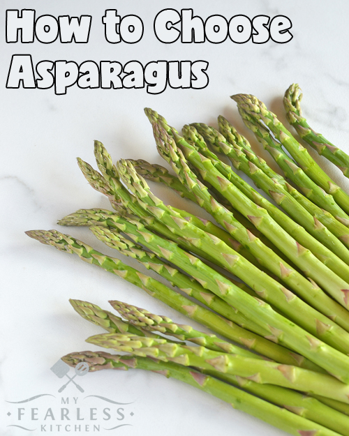 green asparagus spears on a white marble background