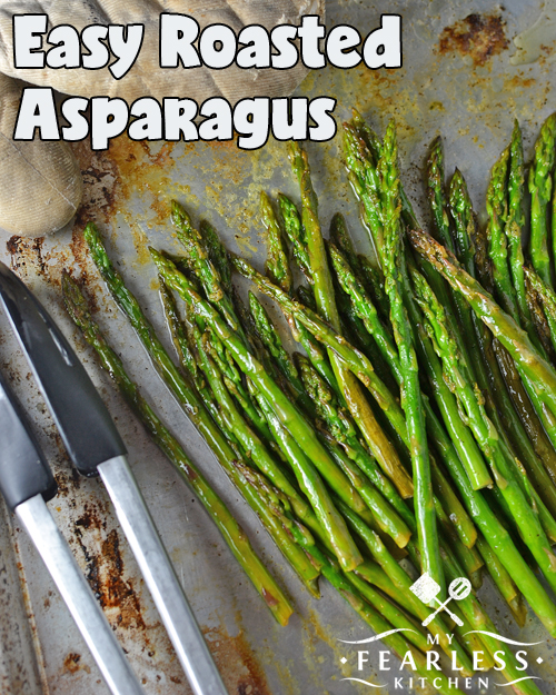 baked asparagus on a baking sheet with tongs