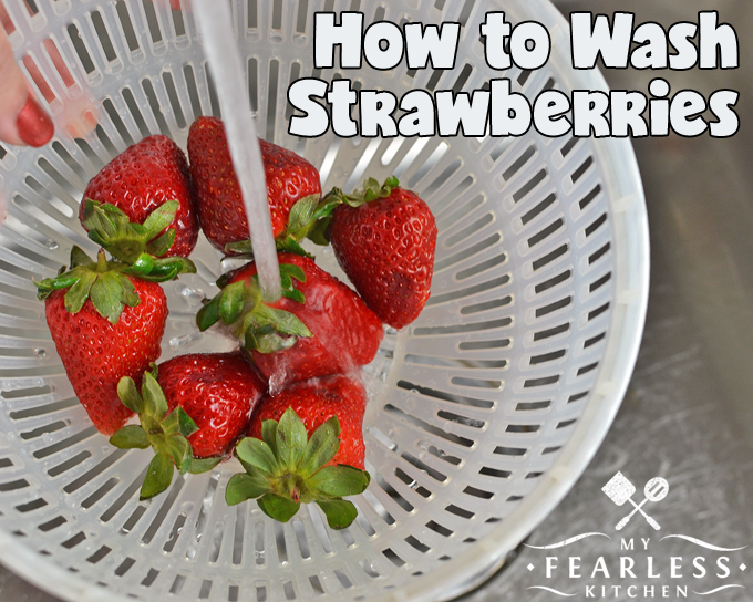running water over strawberries in a white colander